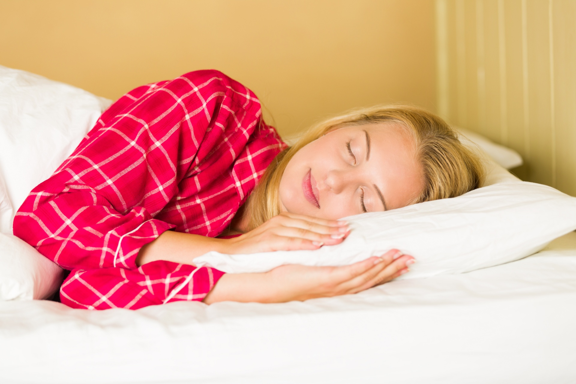A blonde woman in red pajamas sleeps on a bed, which is a big part of learning how to sleep well.