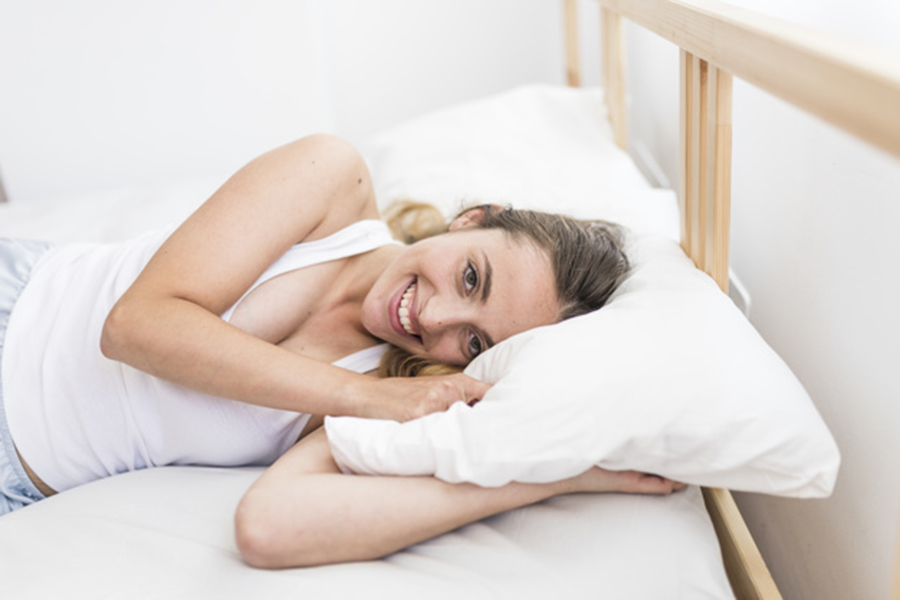 smiling woman with the best pillow on bed