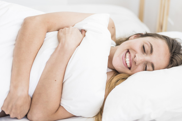 woman hugging pillow while lying on bed