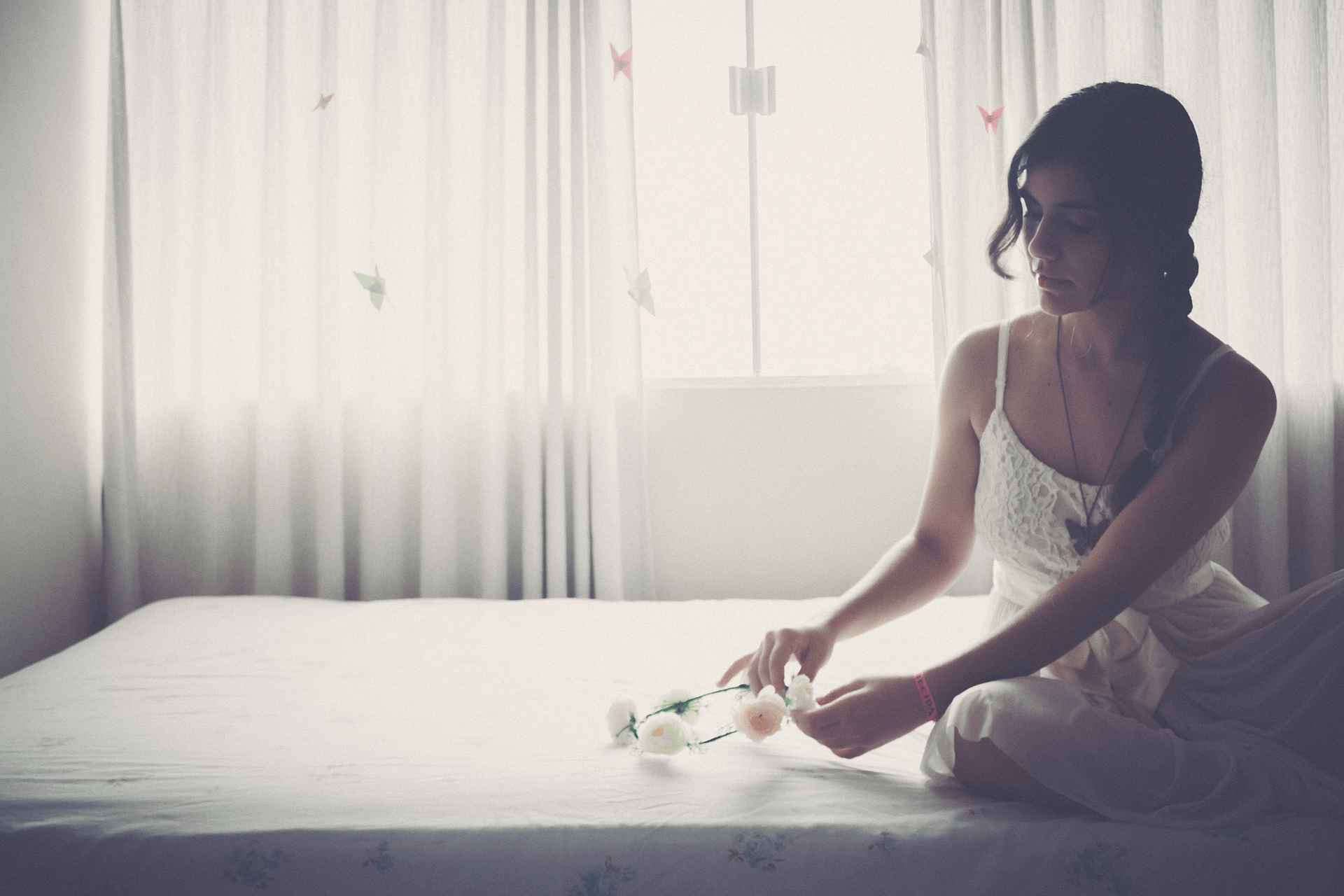 Woman sitting at the best adjustable beds while holding a flower