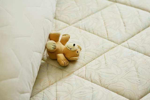 mattress with cover and stuff toy on top